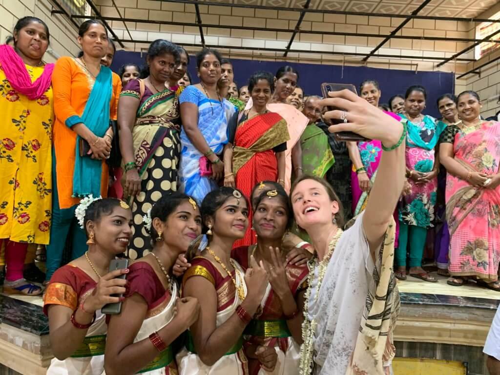 Lana trekt een selfie met jongeren op bezoek in India.