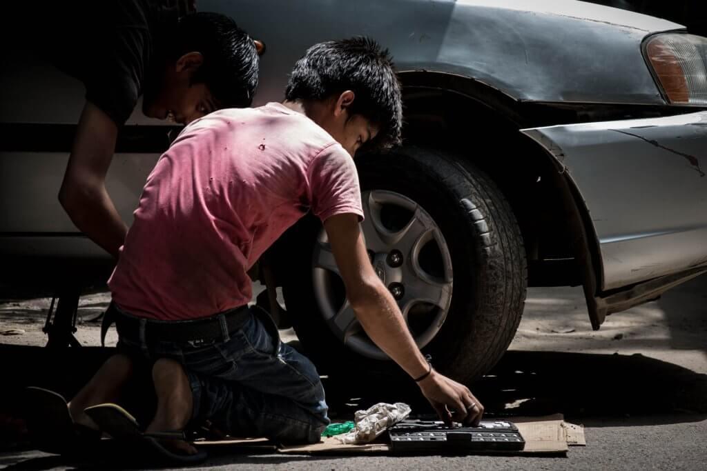 kinderarbeid, jongen werkt aan auto