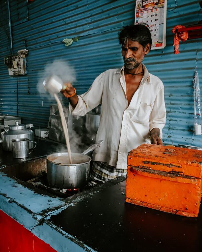 eten in India, man in shop serveert chai tea